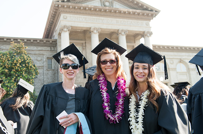 Three female students from the School of Education gather in front of the Administration Building after commencement.