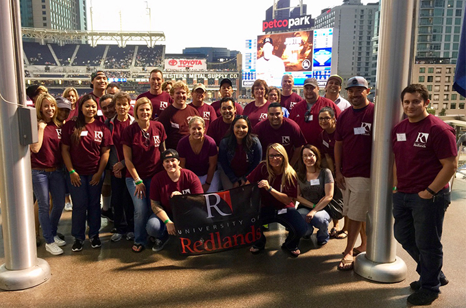 A group of U of R alumni pose together with a U of R flag at a baseball stadium.