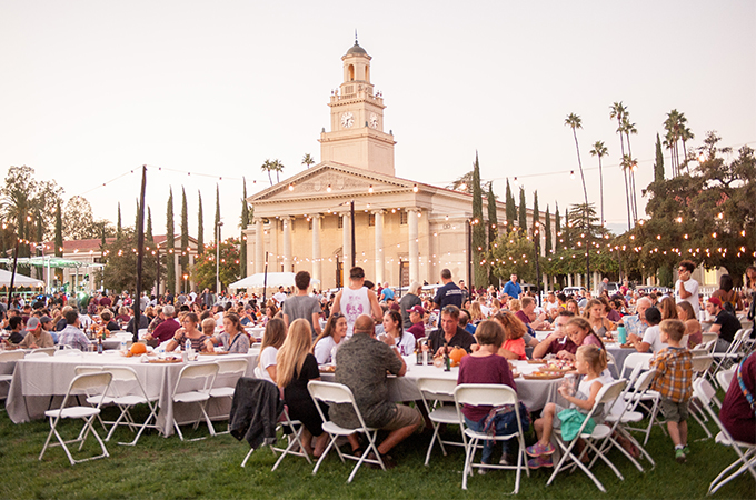 People gather on the Quad lawn during twilight at the University of Redlands during Homecoming weekend.
