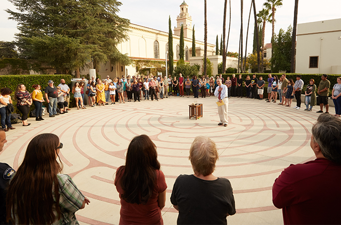 People stand in a circle around the labyrinth at the University of Redlands.