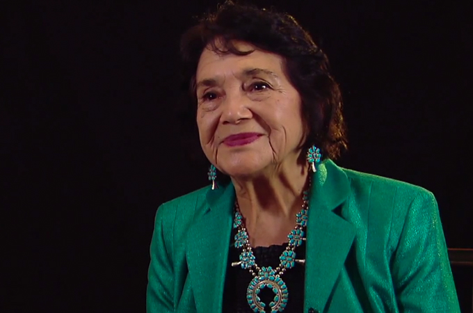Civil rights activist and labor organizer Dolores Huerta smiles in a green outfit.