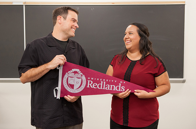 Two people smile at each other in a classroom while holding a pennant flag from the University of Redlands.