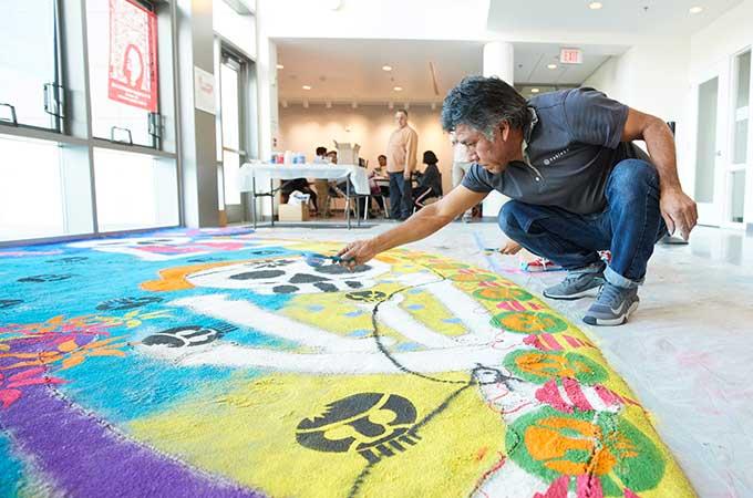 artist sprinkling sand on installation