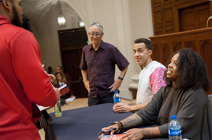 Speakers sit at a table to sign books while greeting members of the audience.