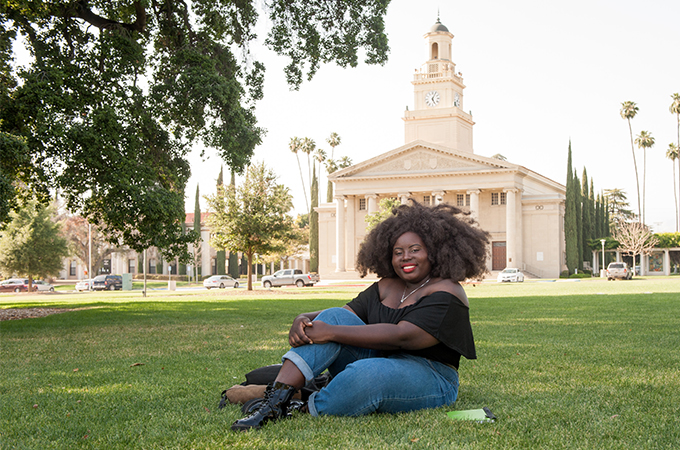 A student sits on the Quad in front of the Memorial Chapel at the University of Redlands.