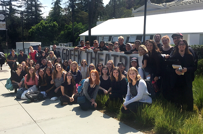 Members of Chapel Singers and Bel Canto choirs stand in front of the Greek Theater sign in L.A.