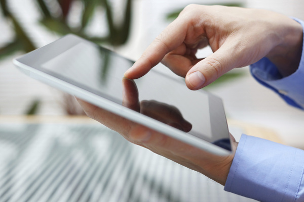 Hand with finger on tablet touch screen